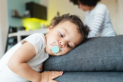 toddler resting head against couch cushions