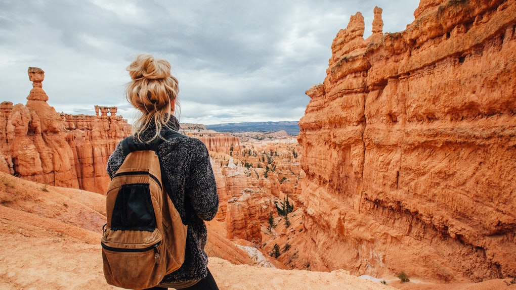 A young woman with blonde hair stands over a canyon in Bryce Canyon National Park with her backpack.
