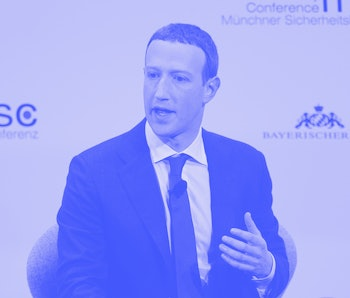 The CEO of Facebook, Mark Zuckerberg is seen mid-speech at a conference. He is wearing a black and white suit with a red tie.