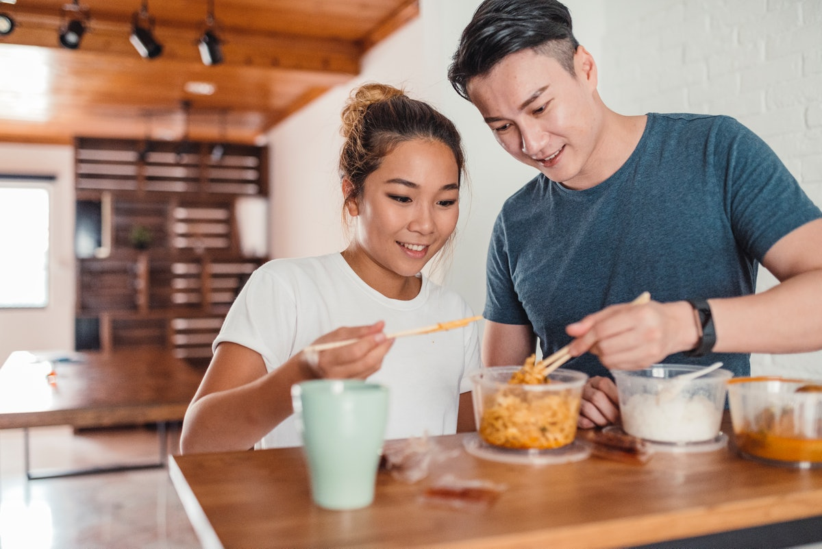 A young Asian couple enjoys takeout food in their kitchen for a fall dinner date at-home.