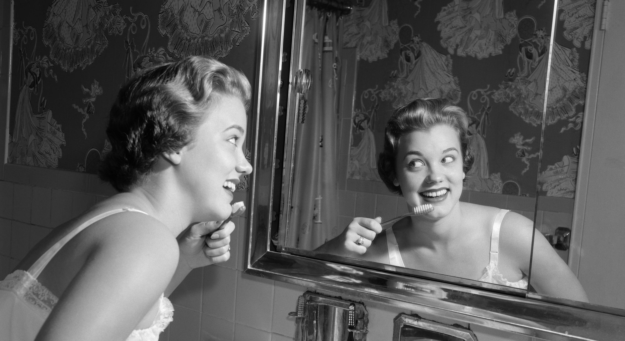 A woman brushes her teeth in the mirror. A dentist told the new york times how much pandemic stress is hurting our teeth.