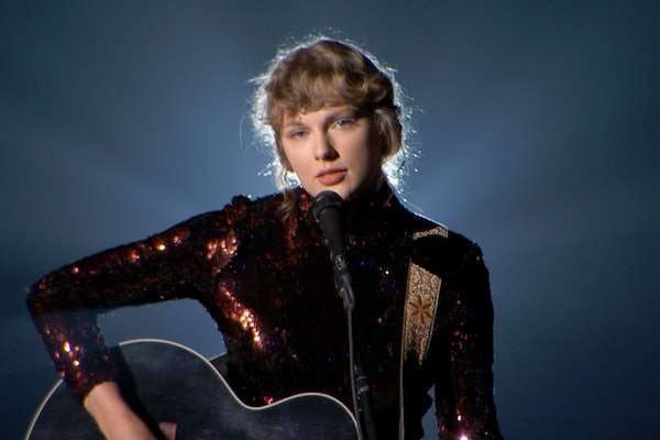 Taylor Swift wears a sequined dress and sings a song while playing guitar.