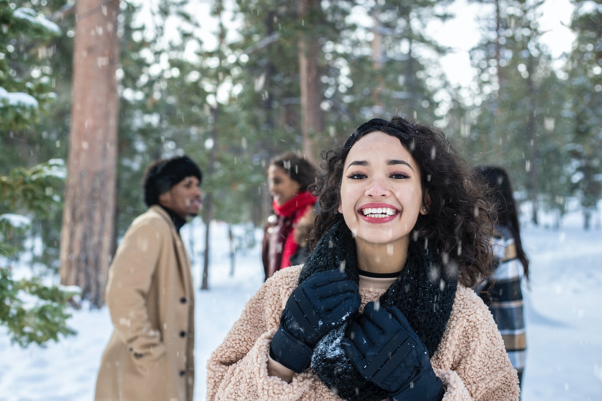 A happy girl stands on a snowy mountain with her friends behind her.