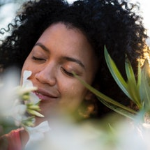 A woman with natural curly hair smells a flower. Here's what covid does to your sense of smell.