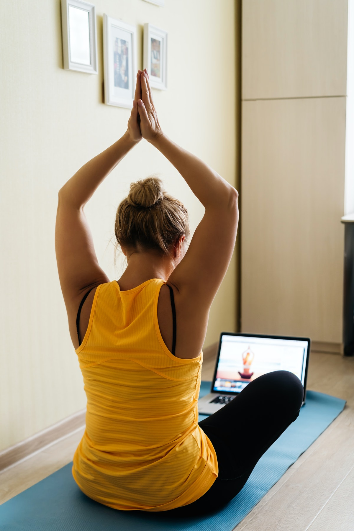 A woman does yoga at home as part of a fake commute.
