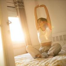 A woman stretches in her bedroom in the morning. Morning stretching routines can help people get their day started.