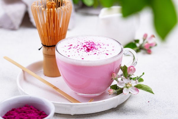 A pink latte sits on a white table with flower garnishes.