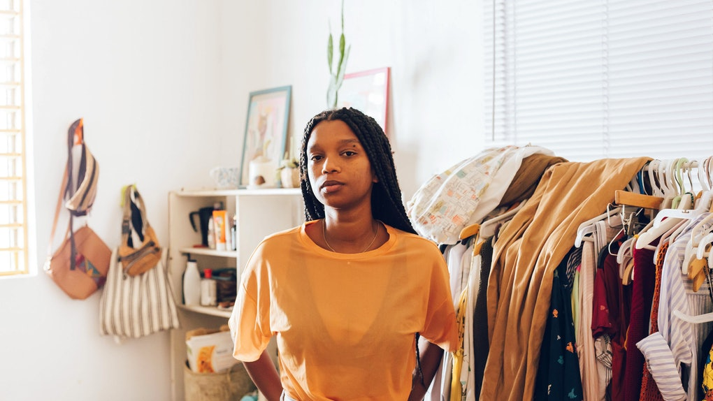 A young Black woman stands in front of a rack of trendy clothes in her home.