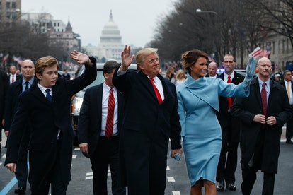 Barron Trump, Donald Trump, and Melania Trump wave while walking from the Capitol building following Trump's swearing in as the 45th president of the United States.