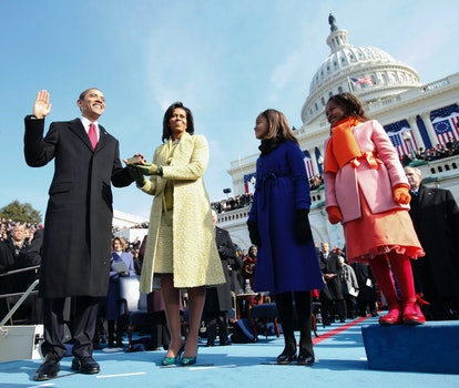 Barack Obama stands outside the Capitol building holding his left hand over a bible being held by his wife, Michelle, while his two daughters stand nearby.