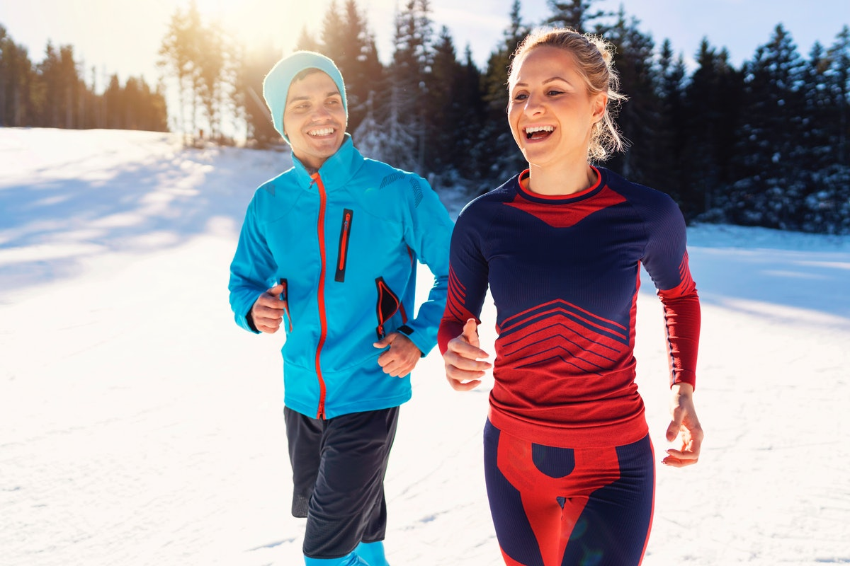 A couple in running gear get out in the snow for a early morning run.