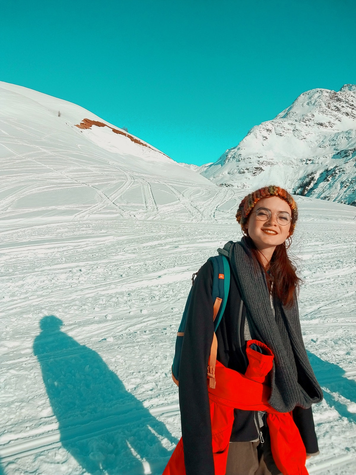 A young woman poses for a picture while on a winter hike in the mountains.