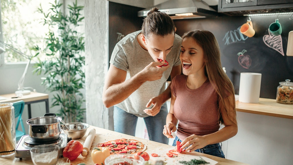A happy couple goofs around while making baguette pizza in their bright kitchen.