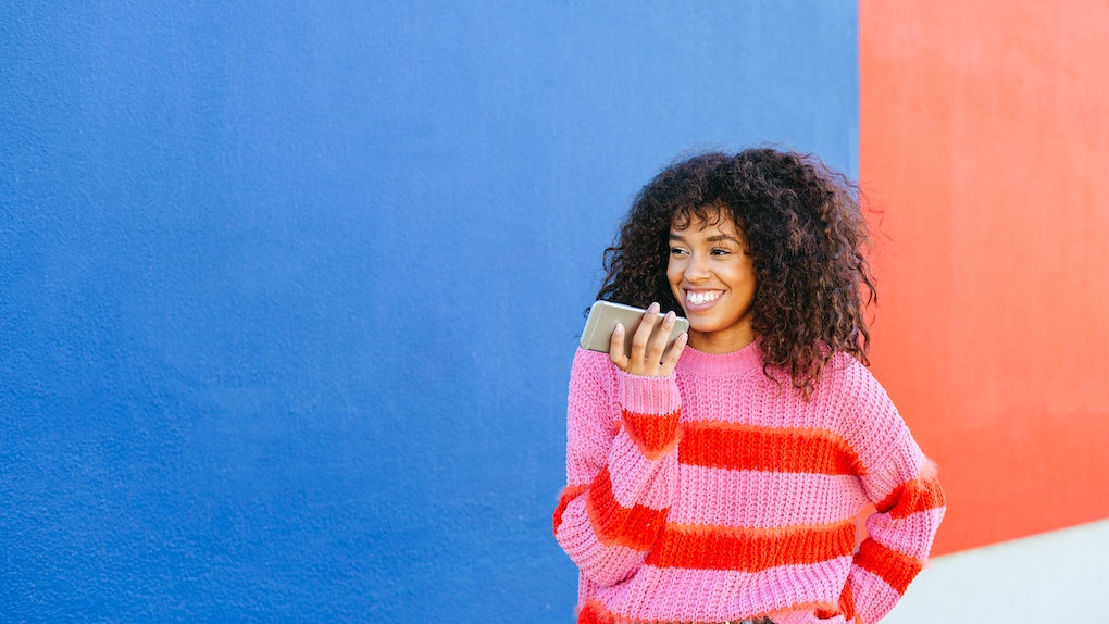 A young Black woman stands in front of a blue and red wall while wearing a colorful sweater and holding an iPhone.