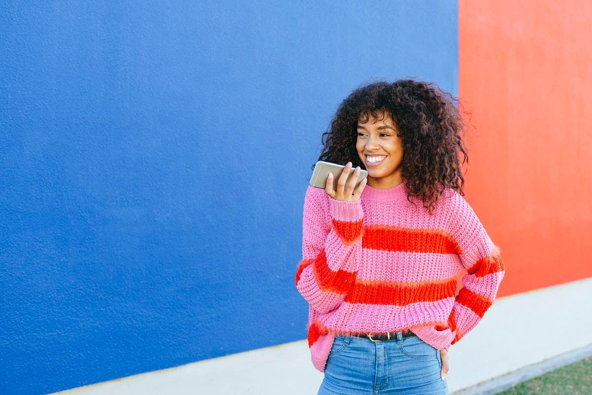 A young Black woman stands in front of a blue and red wall while wearing a colorful sweater and hold...