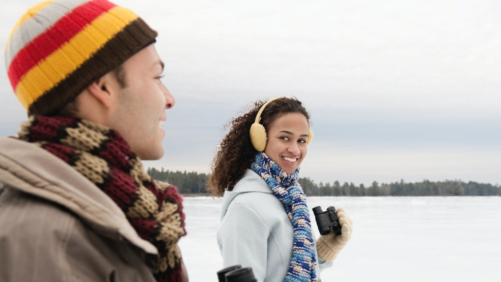 A young couple takes a winter hike with binoculars on a cloudy day.