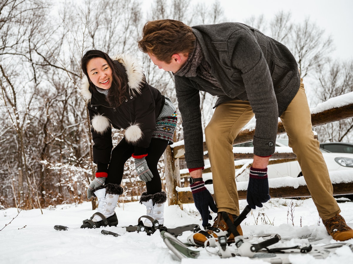 A happy couple adjusts their snowshoes in the snow.