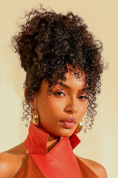 Yara Shahidi's natural curtain bangs frame her face perfectly with curly tendrils.