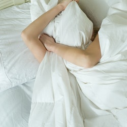 A woman in white sheets pulls the covers over her face after a night of drinking while she's dealing...