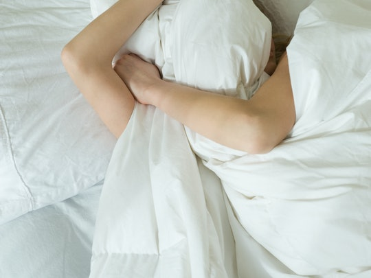 A woman in white sheets pulls the covers over her face after a night of drinking while she's dealing with hangxiety. Experts explain how to deal with hangover anxiety before it happens.