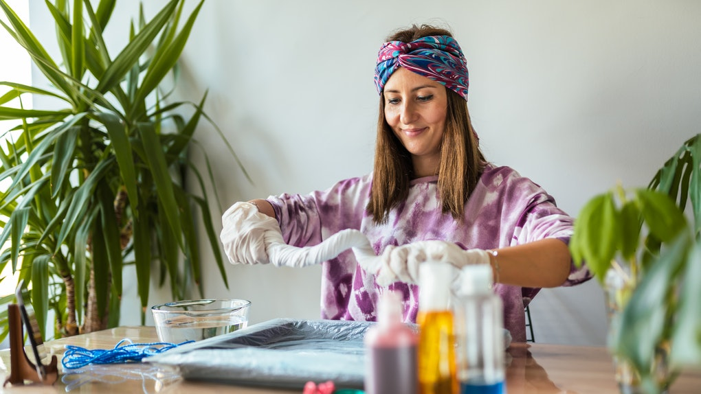 A young woman bleach tie-dyes clothes in her living room.
