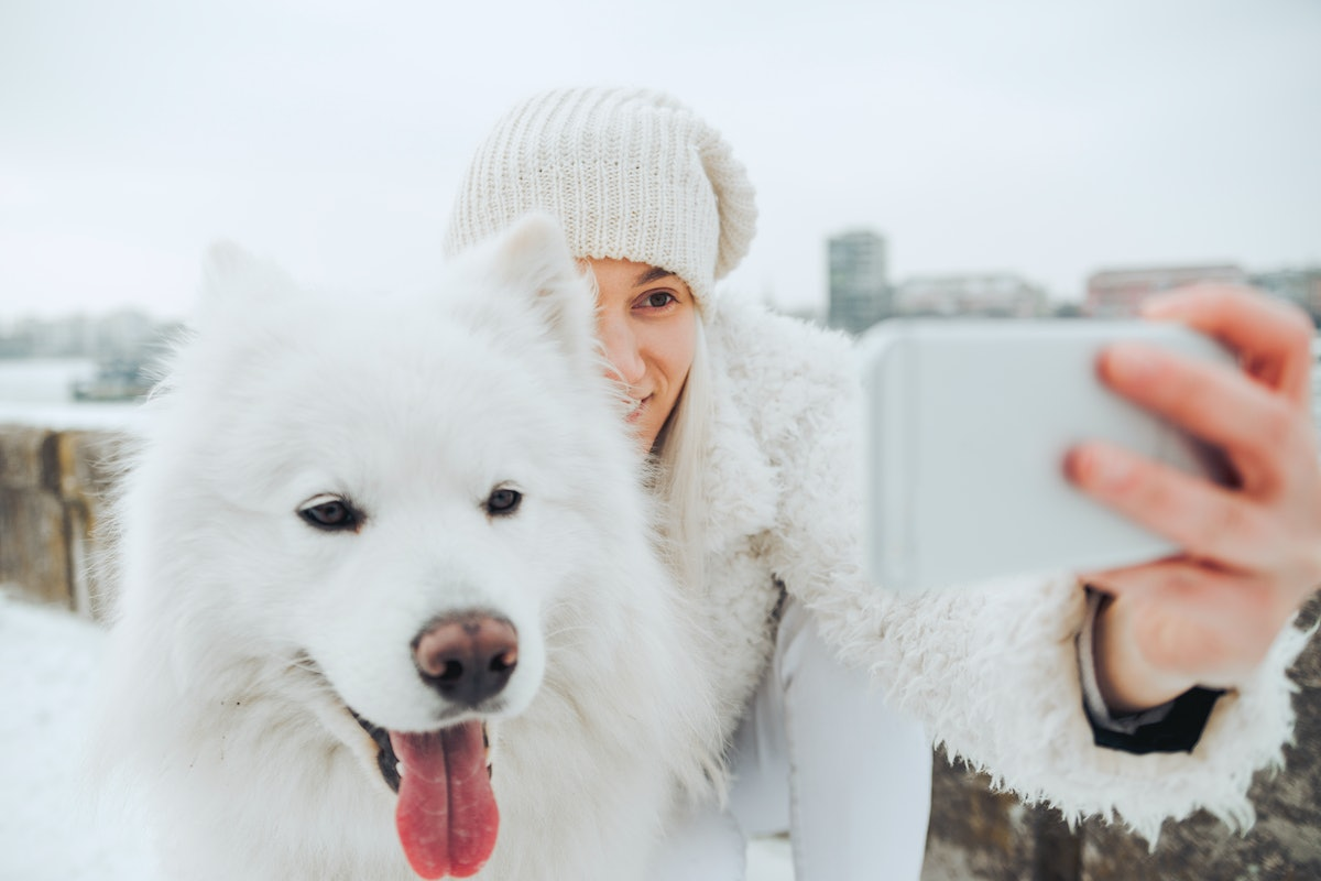 A young woman poses for a selfie with her dog in the middle of winter.