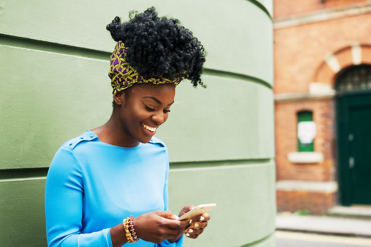A happy woman wearing a blue long-sleeve shirt smiles while she texts on a sunny day.