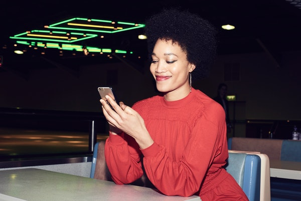 A young Black woman looks at her phone while sitting in a diner at night.