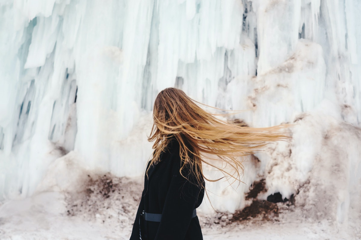 A stylish woman with blonde hair looks away from the camera as the wind blows.