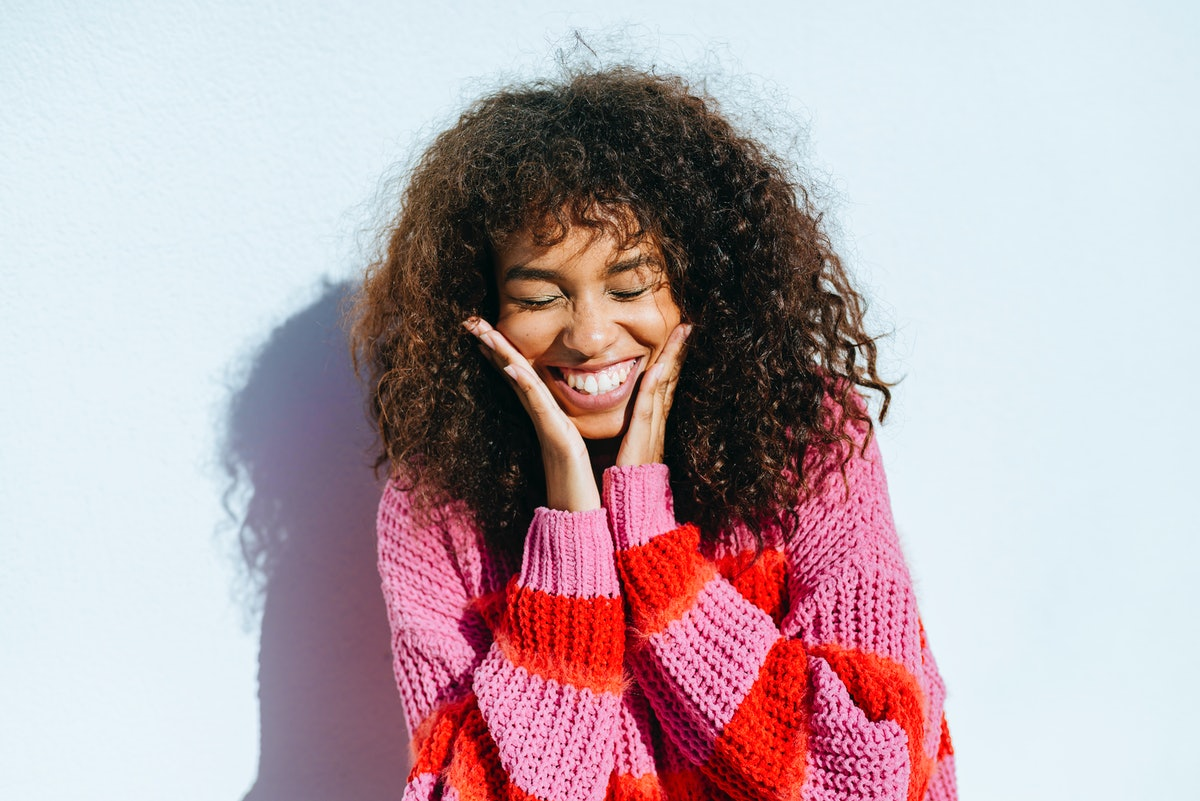 A young woman with curly hair smiles wide for a camera, while wearing a pink and red sweater.