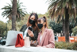 Two people wearing masks look at one of the people's phone outside near palms trees. Keep your masks on when you see your vaccinated friends.