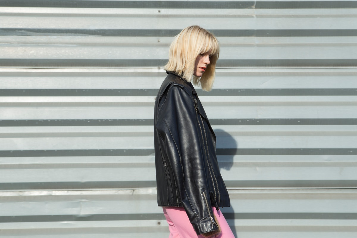 A blonde woman looks to the side while showing off her haircut and wearing a leather jacket and brig...