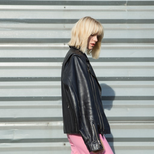 A blonde woman looks to the side while showing off her haircut and wearing a leather jacket and bright pink pants.