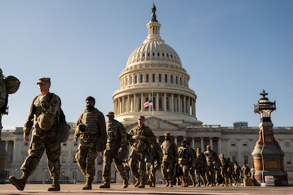 Members of the National Guard march in on the grounds of the US Capitol