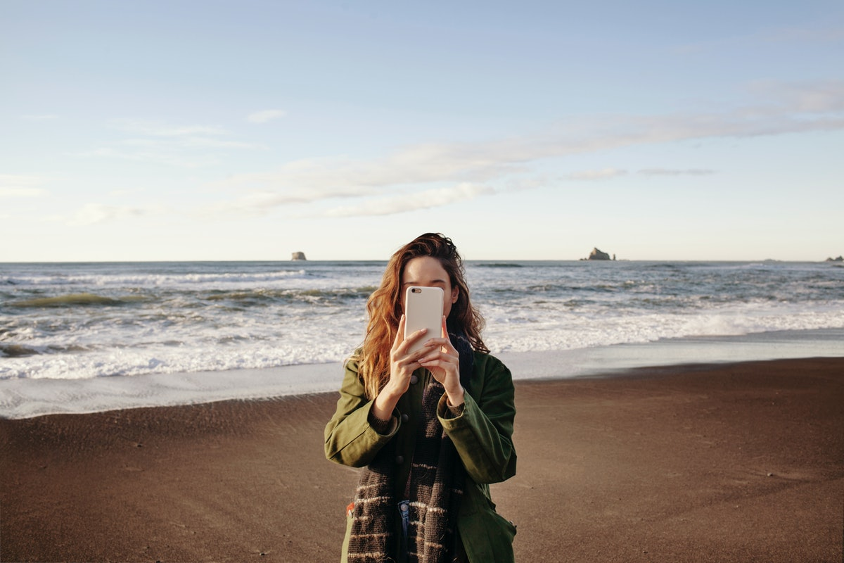 A young woman stands in front of an ocean in the winter and holds up her phone.