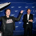 Tesla CEO Elon Musk stands in front of a model rocket.