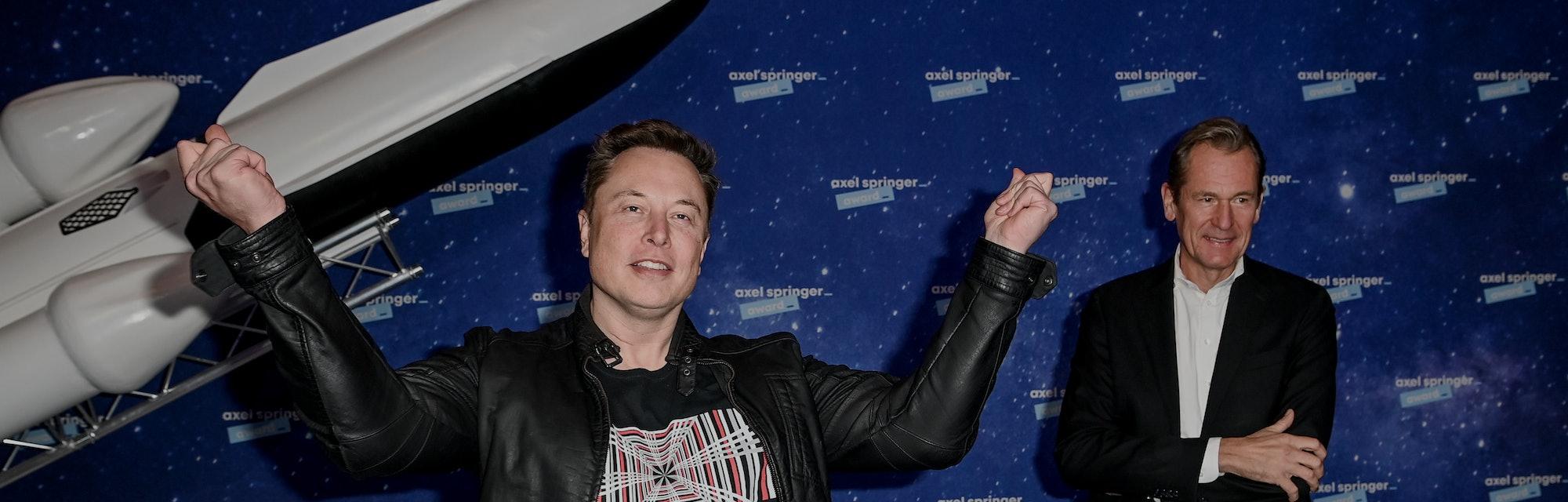 Tesla CEO Elon Musk stands in front of a model rocket.