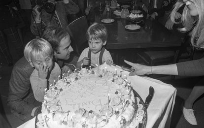 Joe Biden blows out candles on a cake with sons Beau and Hunter standing on each side of him in this black and white photo.