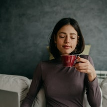 A woman wearing a blanket drinks a mug of tea. If you get cold easily it could be a sign of 9 health issues.