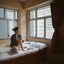A person sits on a bed looking out the window. It's normal to feel sad, even during happy times.