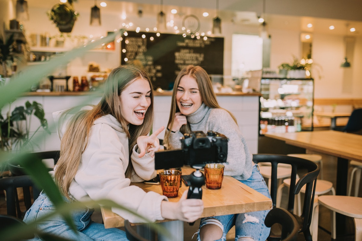 Two friends laugh and take selfies in a coffee shop.