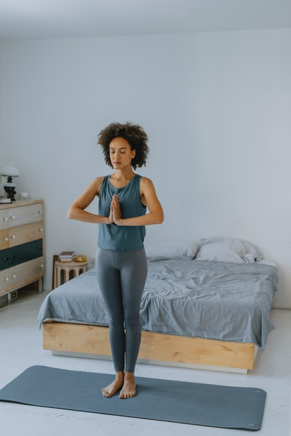 A woman stands with her hands at heart center doing yoga in the morning.