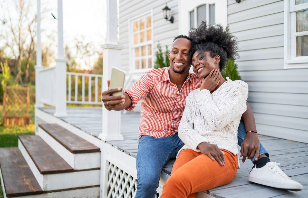 A happy couple snap a selfie on a spring afternoon on their back porch.