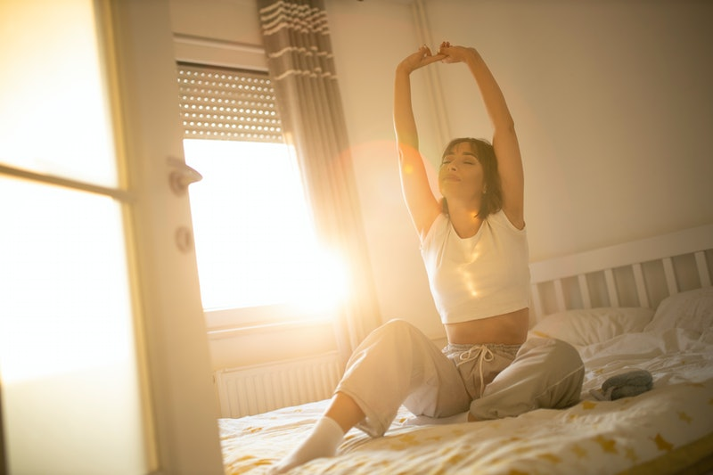 A person sits up in bed and stretches with light streaming through the window. Waking up can be tough, so TikTok has some morning routine ideas for you.