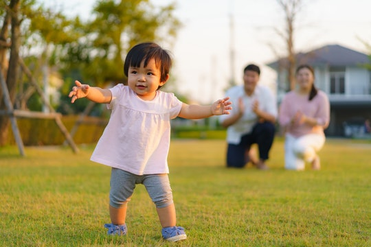 A toddler, bathed in sunlight, walks across a lawn, her parents visible in the background.