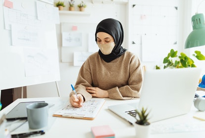 A woman wearing hijab wears a mask at an office. Can your job force you to be vaccinated before going back to work? Doctors explain.