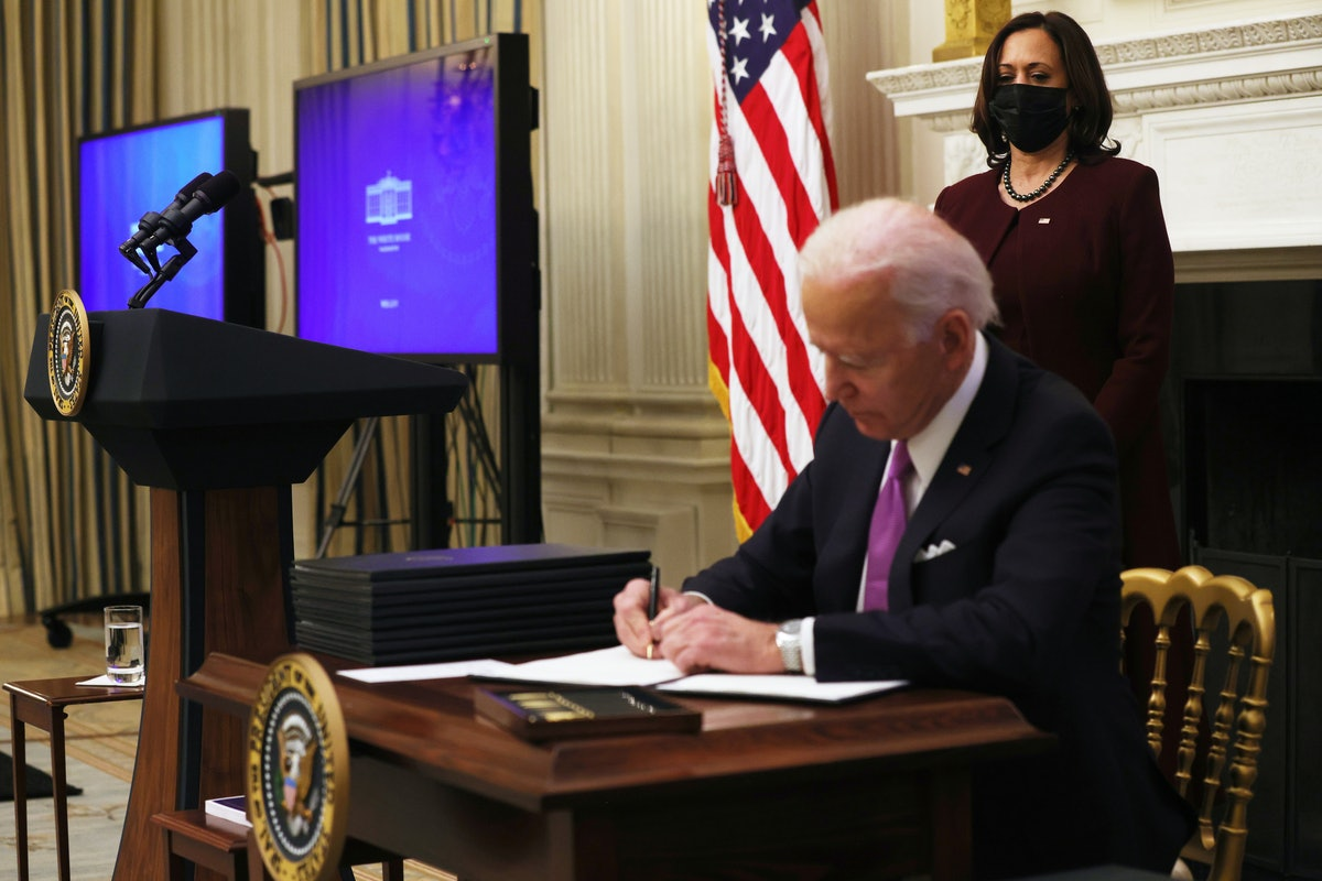 President Biden signs executive orders while Vice President Harris looks on. Former President Trump had no COVID vaccine distribution plan.