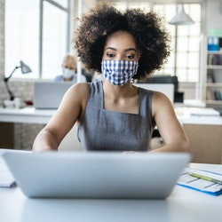 A woman wearing a gingham mask works at a laptop. Can your job force you to get vaccinated for covid...