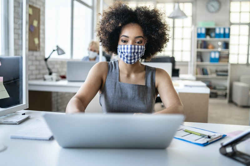 A woman wearing a gingham mask works at a laptop. Can your job force you to get vaccinated for covid to go back to work?