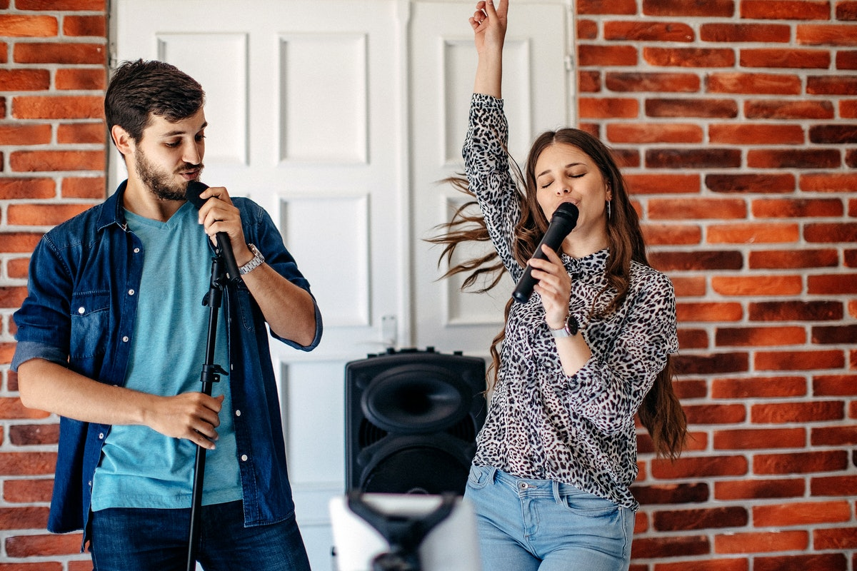 Two friends enjoy a round of karaoke in a trendy space with exposed brick.